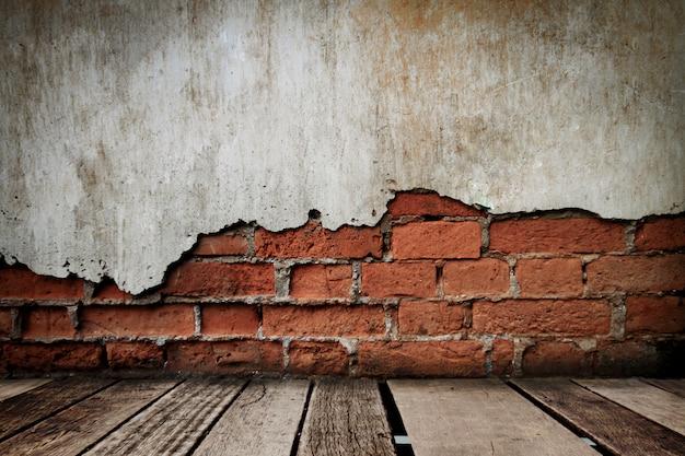 Piso de madeira no antigo quarto com parede de tijolos, fundo sujo