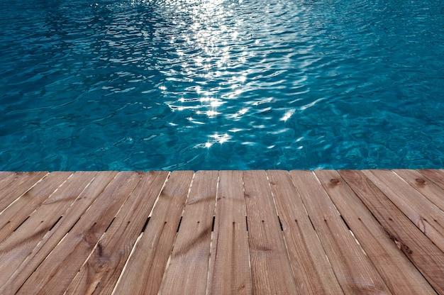 Piso de madeira velho e água azul na piscina.