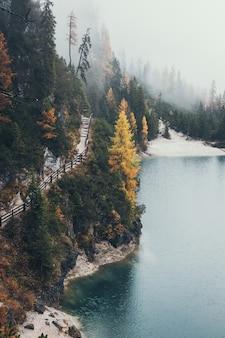 Pista de caminhada ao redor do lago di braies em uma manhã de nevoeiro na temporada de outono