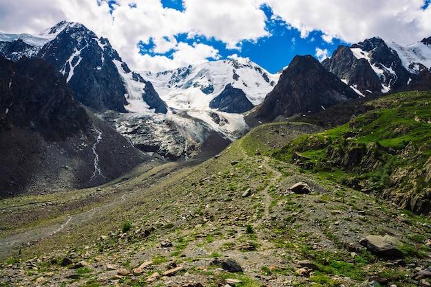Pista de caminhada leva a enormes montanhas nevadas em dia ensolarado.