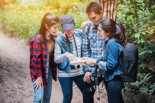 Pista de caminhada na floresta com amigos. caminhe pelo campo e leia o mapa. trabalho em equipe ao ar livre.