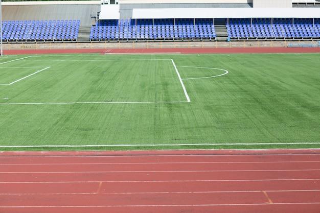 Pista de corrida e campo com grama verde para futebol no estádio