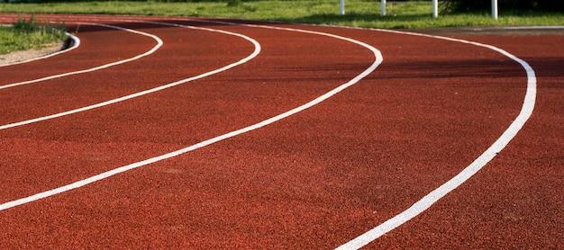 Pista de corrida no estádio. revestimento de borracha. esteira ao ar livre. conceito de estilo de vida saudável. treino cardio de atletas