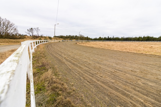Pista de corrida vazia para cavalos de corrida, pista de areia e cerca branca