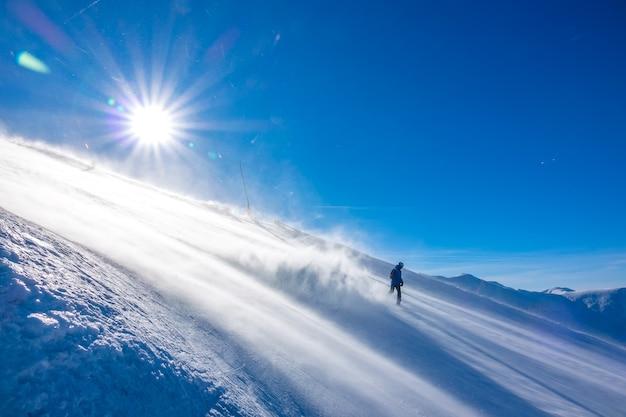 Pista de esqui íngreme com tempo ensolarado e ventoso. um snowboarder solitário e irreconhecível desce e pega muito pó de neve na luz do sol