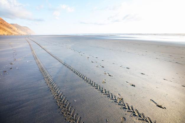 Pista de pneu de carro off road na praia de areia, com oceano e céu azul. costa oceânica da nova zelândia