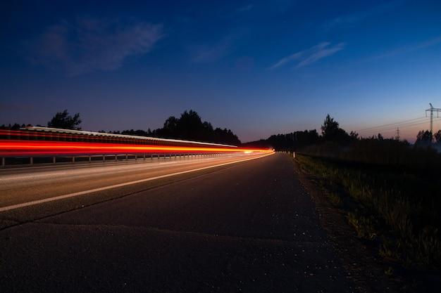 Pista noturna com luzes desfocadas dos faróis dos carros. longo tempo de exposição.