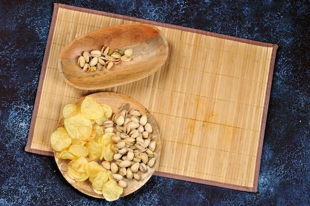 Pistache e batatas fritas em uma placa de madeira sobre um fundo azul escuro