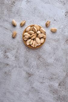 Pistache orgânico em uma tigela de madeira na mesa cinza. vista superior, espaço para texto