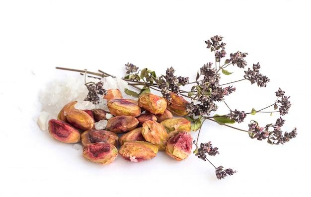 Pistácios com casca e pistácios pelados com grandes cristais de sal e ervas aromáticas secas no fundo branco