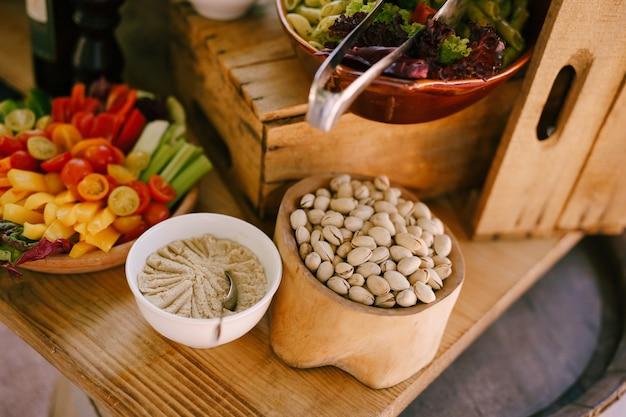 Pistácios em um prato de madeira sobre uma mesa com patê de alface com macarrão e vegetais fatiados