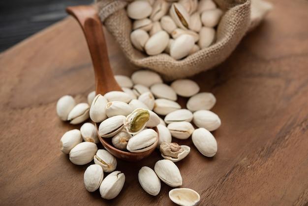 Pistácios em uma colher de pau. saco com pistache sobre uma mesa de madeira.