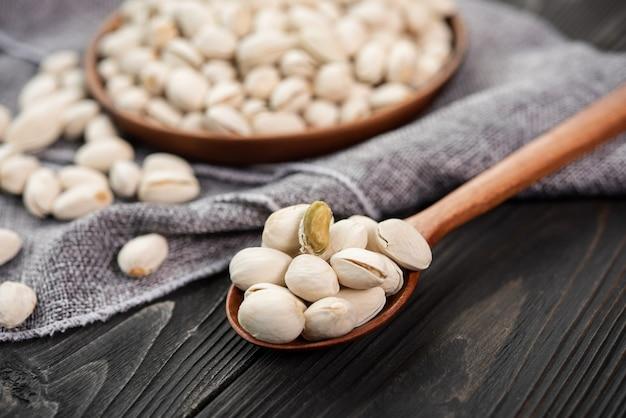 Pistácios em uma colher de pau. tigela de madeira com pistache de nozes. sobre um fundo de madeira. alimentação saudável e lanche, comida vegetariana orgânica.