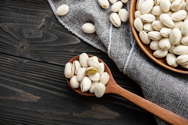 Pistácios em uma colher de pau. tigela de madeira com pistache de nozes. sobre um fundo de madeira, perto de um saco de estopa. alimentação saudável e lanche, comida vegetariana orgânica.