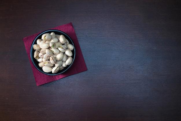Pistácios em uma tigela de cerâmica na mesa de madeira. fundo da mistura alimentar, vista superior, espaço de cópia, banner