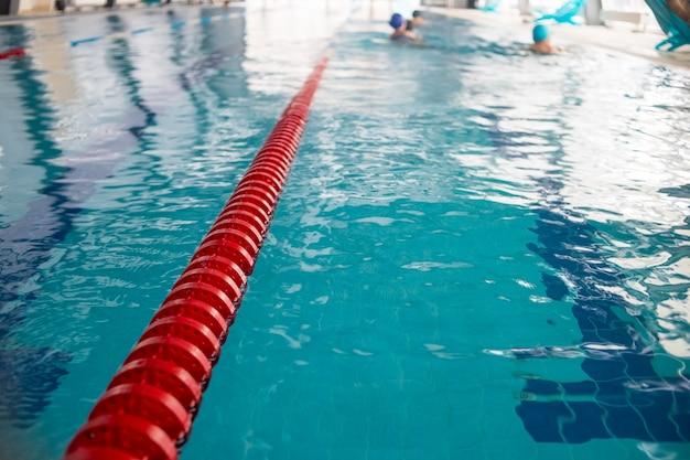 Pistas de piscina na piscina de competição. faixa de corda plástica vermelha na competição de esporte de piscina coberta de água azul