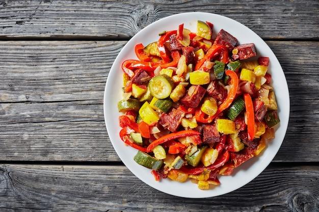 Pisto manchego espanhol - ensopado de legumes com chouriço frito em um prato branco sobre uma mesa de madeira rústica, vista de cima, espaço vazio, flatlay