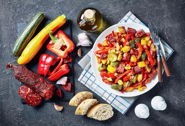 Pisto manchego espanhol - ensopado de vegetais com chouriço frito em um prato branco sobre uma mesa de concreto com ingredientes, vista de cima, close-up, camada plana