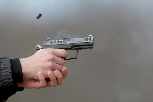 Pistola atirando com as duas mãos, os projéteis emanando da veneziana e fumaça azul.