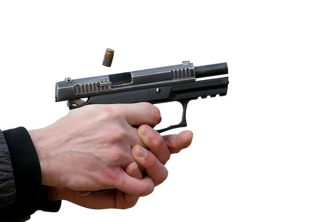 Pistola atirando com as duas mãos, os projéteis emanando da veneziana e fumaça azul