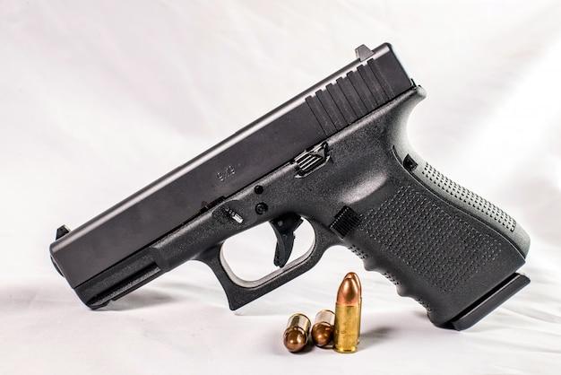 Pistola de 9 mm e balas espalhadas com munição em fundo de madeira
