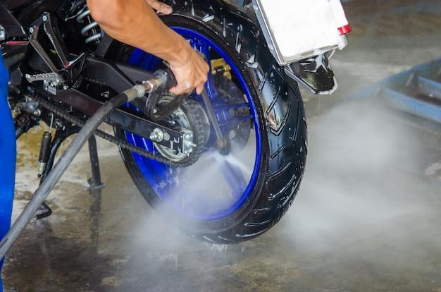 Pistola de água de alta pressão lavando uma motocicleta