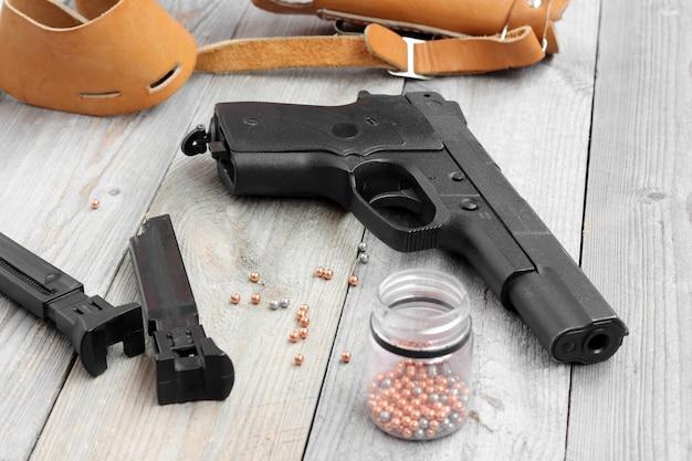 Pistola de ar, dois clipes, coldre e bolas para atirar em uma mesa de madeira.