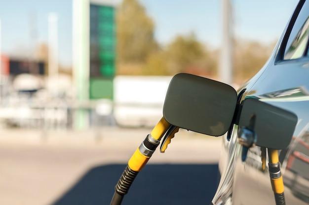 Pistola de combustível no tanque do carro carro no posto de gasolina