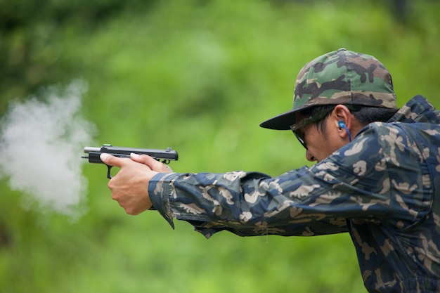 Pistola de objetivo de aplicação da lei por duas mãos no campo de tiro da academia em flare