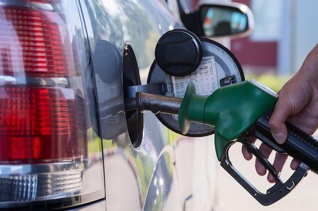 Pistola de posto de gasolina na mão do motorista. bomba de posto de gasolina moderna, excelente design para qualquer finalidade. o motorista do carro.