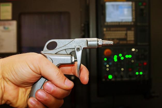 Pistola de sopro, pistola do compressor de ar em mãos na fábrica.