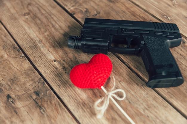 Pistola e amor coração vermelho em fundo de madeira