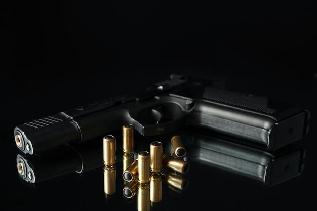 Pistola e balas na mesa de espelho contra preto