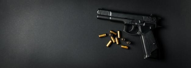 Pistola e balas traumáticas no preto. arma de defesa pessoal