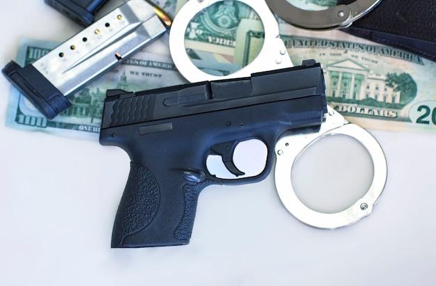 Pistola e munições de 9 mm de balas, algemas e notas de dólar americano em fundo branco. punição e dinheiro criminoso, vista superior, espaço de cópia para texto. dólares americanos, banner de crime financeiro
