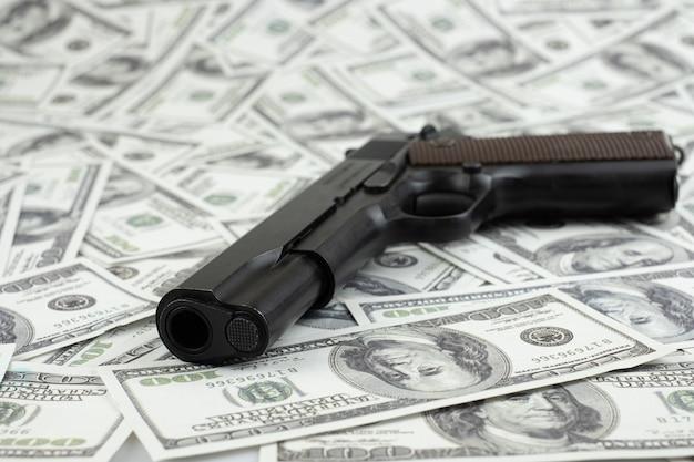 Pistola preta na pilha de dinheiro fundo de 100 dólares