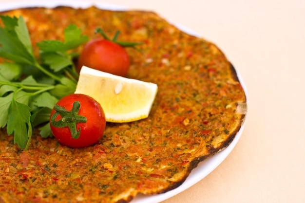Pita de tortilla turca com carne picada e especiarias, decorada com tomates cereja