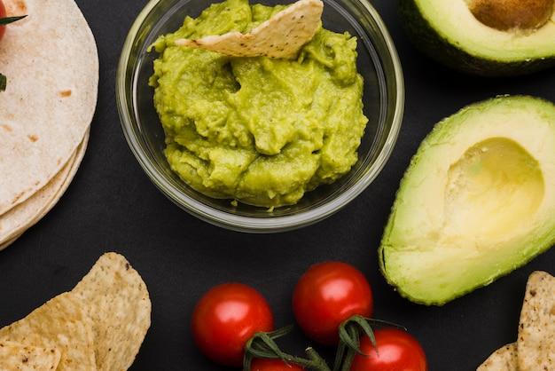 Pita perto de legumes e molho com nachos