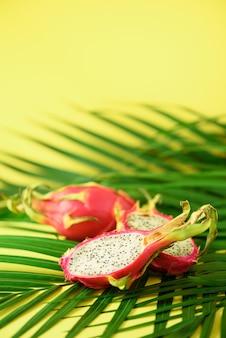Pitahaya ou fruta do dragão sobre as folhas de palmeira verdes tropicais. pop art design, conceito criativo de verão.