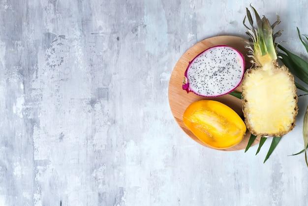 Pitaya ou fruta do dragão com folha de palmeira na placa redonda de madeira no fundo de pedra cinza com espaço de cópia, lay plana