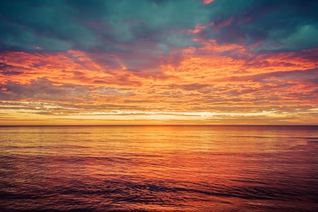 Pitoresco nascer do sol sobre o mar. céu dramático colorido em laranja e vermelho.