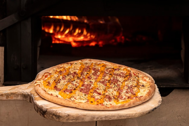 Pizza à brasileira entrando no forno a lenha. foco seletivo