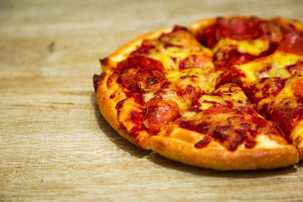 Pizza americana com pepperoni em uma mesa de madeira.
