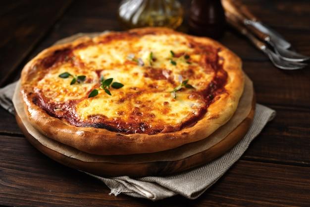 Pizza apetitosa margherita no fundo escuro de madeira