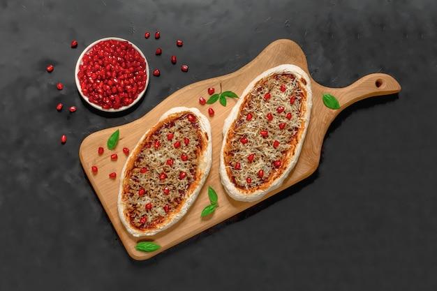 Pizza árabe em um carrinho de madeira. scones com carne picada e romã.