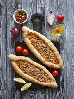 Pizza árabe lahmacun em uma mesa de madeira.