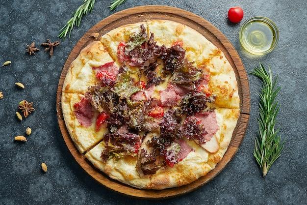Pizza assada caseira com tomate, frango, alface, crutão, molho vermelho e bacon em uma superfície preta em uma composição com ingredientes