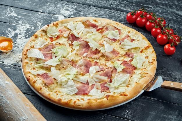 Pizza assada com alface, croutons, molho branco e frango. pizza caesar em uma mesa de madeira preta em uma composição com ingredientes. vista do topo
