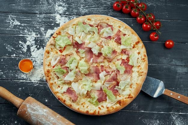 Pizza assada com alface, croutons, molho branco e frango. pizza caesar em uma superfície de madeira preta em uma composição com ingredientes. vista do topo