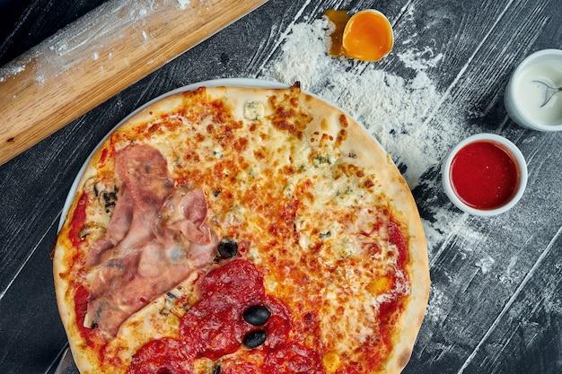 Pizza assada com salame, presunto e frango com molho vermelho e queijo derretido em uma mesa de madeira preta em uma composição com ingredientes. vista do topo